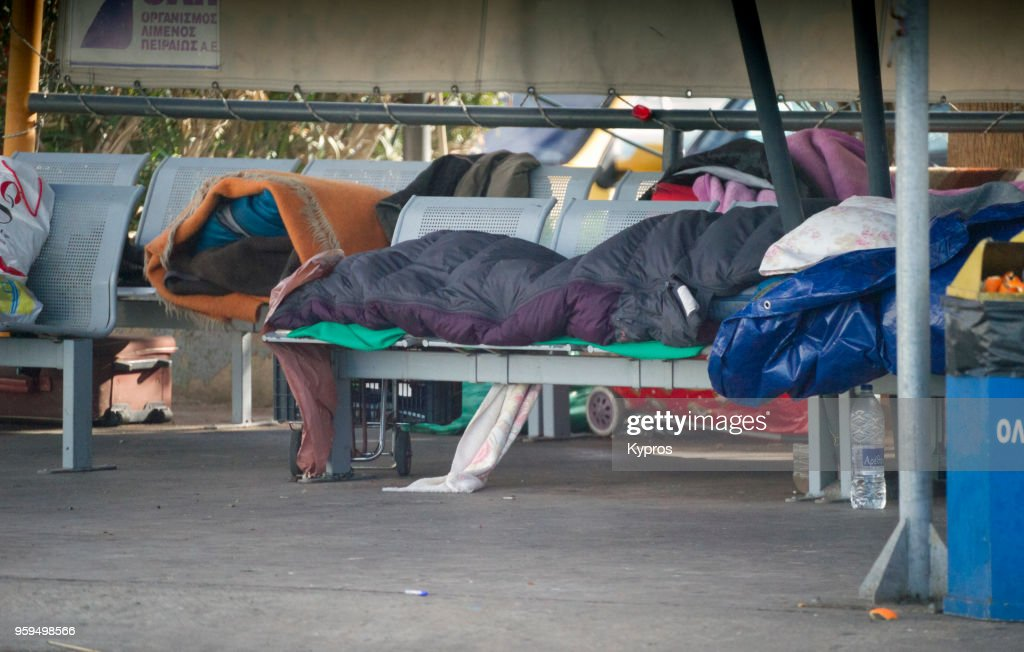 Europe, Greece, Athens, Piraeus Area, January 2018: View Of Homeless Men Asleep On Benches At The Port During Winter : Stock-Foto