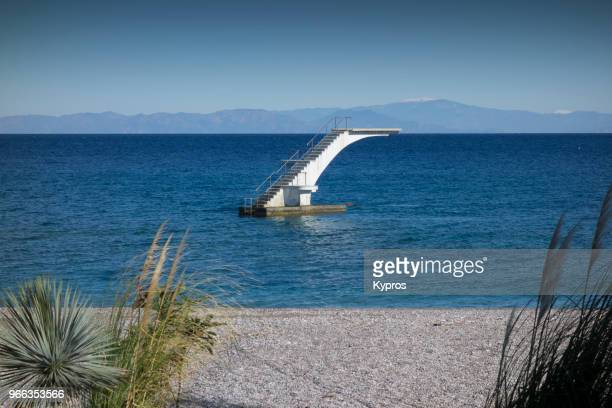 europe, greece, rhodes island, 2017: view of diving board near stony beach - dodecanese islands stock photos and pictures