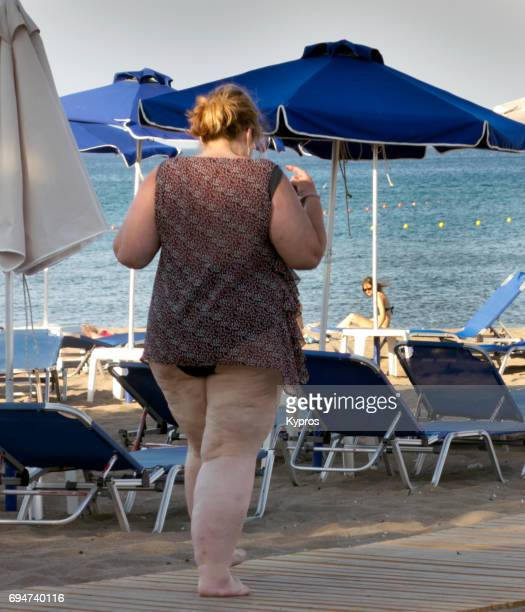europe, greece, rhodes island, faliraki beach, view of overweight woman walking at seaside - fat woman at beach stock photos and pictures