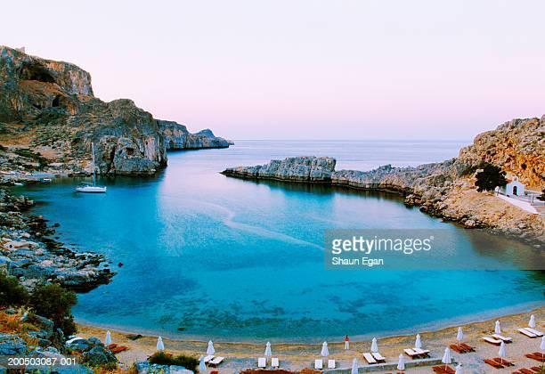 europe, greece, rhodes, lindos, picturesque bay with beach and anchored sailboat - lindos stockfoto's en -beelden