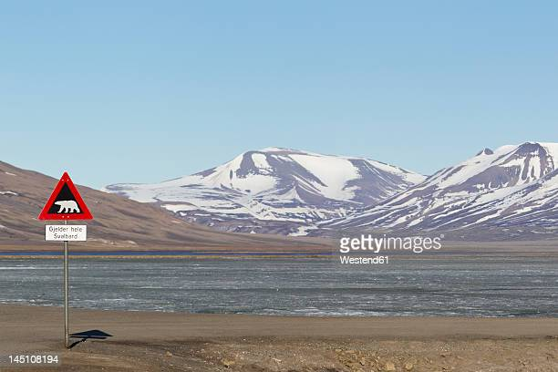 Europe, Norway, Spitsbergen, Svalbard, Longyearbyen, Polar bear sign with reservoir in background