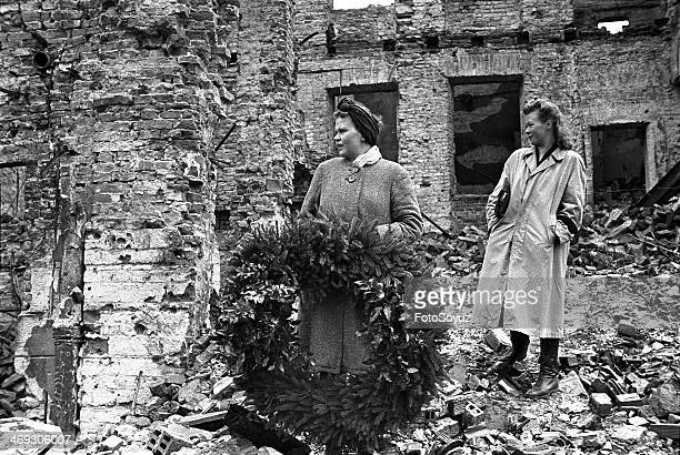 Liberation of Warsaw Women with a wreath near the buildings damaged after intensive bombing raid