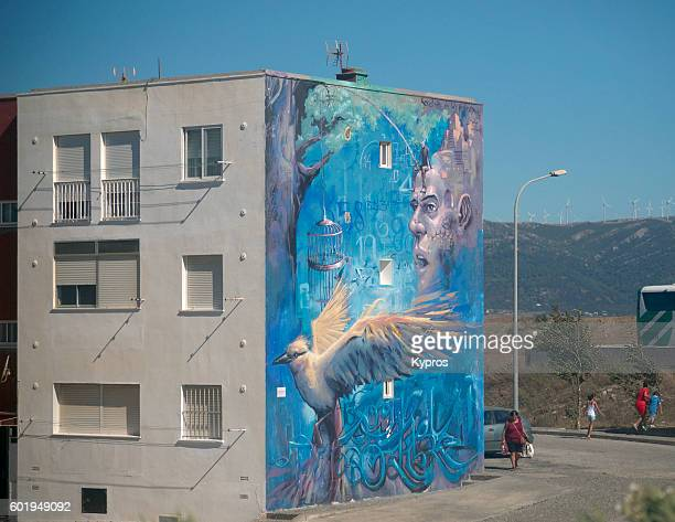 Europe, Spain, Cadiz, Andalusia, Tarifa Area, View Of Apartment Building Painted With Street Art Mural. Four Artists (Vincent Abadie Hafez, Abdelatif Moustad, Raúl Ruiz, And Alejandro Hugo Dorda Mevs) Created The Project B On The Theme 'Cross-Border'. In