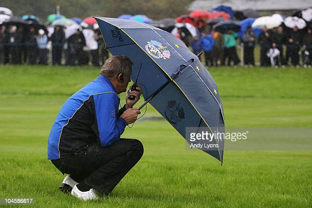 Europe Team Captain Colin Montgomerie waits on the fourth hole as rain falls during the Morning Fourball Matches during the 2010 Ryder Cup at the...