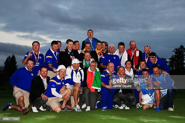 Europe team captain Paul McGinley celebrates winning the Ryder Cup trophy with his team and their caddies after the Singles Matches of the 2014 Ryder...