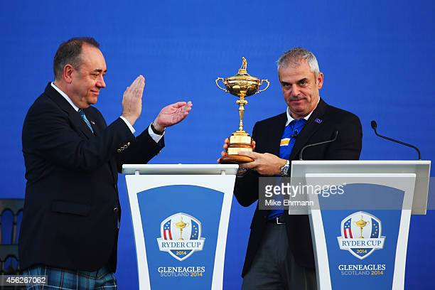 Europe team captain Paul McGinley is presented with the Ryder Cup trophy by Alex Salmond First Minister of Scotland after the Singles Matches of the...