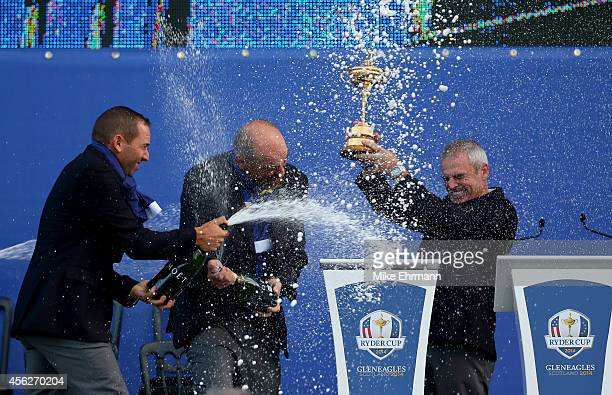 Europe team captain Paul McGinley lifts the Ryder Cup trophy as he is sprayed with champagne by Sergio Garcia of Europe after the Singles Matches of...