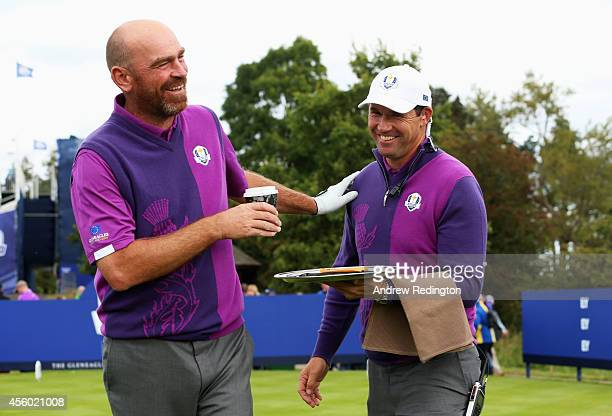 Europe team vice captain Padraig Harrington acts as a waiter for Thomas Bjorn of Europe during practice ahead of the 2014 Ryder Cup on the PGA...