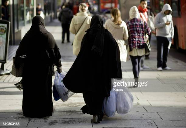 Europe, UK, England, London, View Of Two Muslim Women Wearing Burka's Cruising Edgware Road Carrying Plastic Shooting Bags