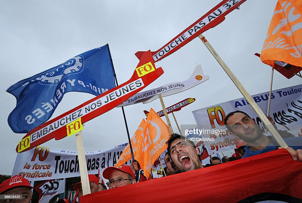 European aircraft manufacturer Airbus employees demonstrate on April 23, 2010 in Toulouse, southwestern France, in front of the entrance of their company to ask for better rise of their wage. Banner at C reads 'Give jobs to young people'.