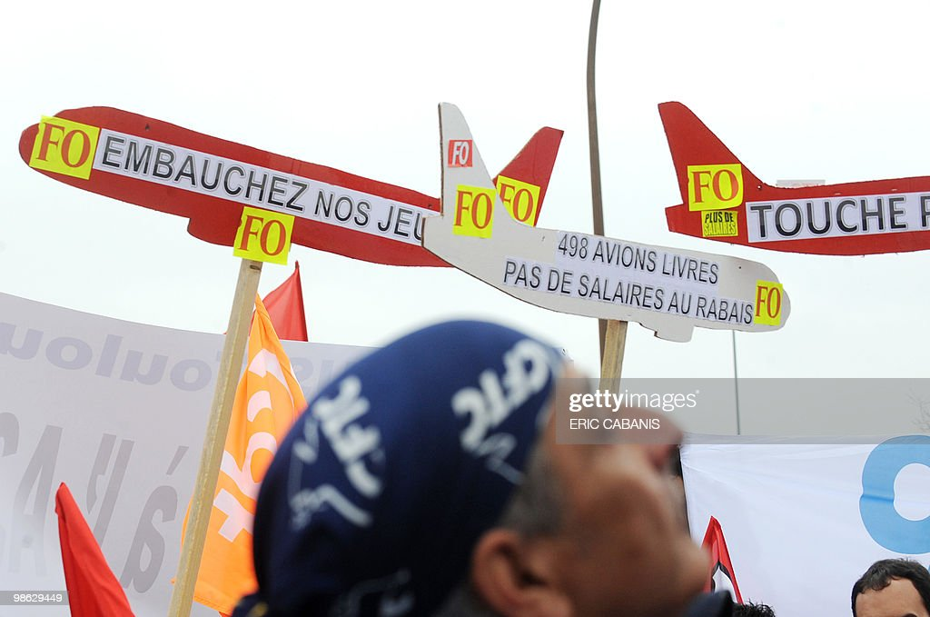 European aircraft manufacturer Airbus employees demonstrate on April 23, 2010 in Toulouse, southwestern France, in front of the entrance of their company to ask for better rise of their wage. Banners with an airplane shape reads, From L, 'Give jobs to our young people', '498 planes delivered, no discount wages', 'Don't touch the Airbus A320'.