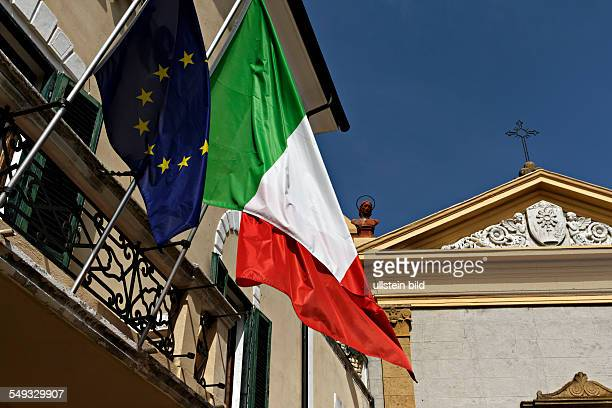 European and Italian flags hanging from town hall Tuscany Italy