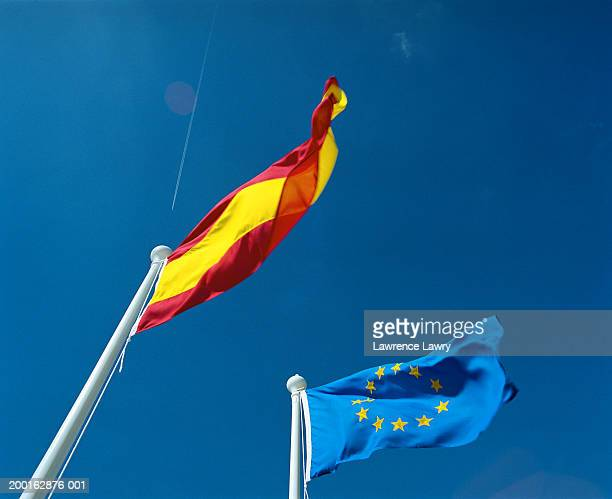 European and Spanish flags blowing in wind, low angle view