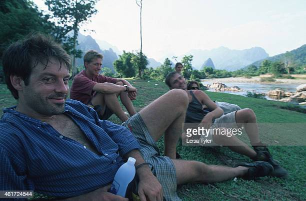 European backpackers resting by the side of the river in Vang Vieng. Scenically spectacular, Vang Vieng is home to a series of limestone outcrops...