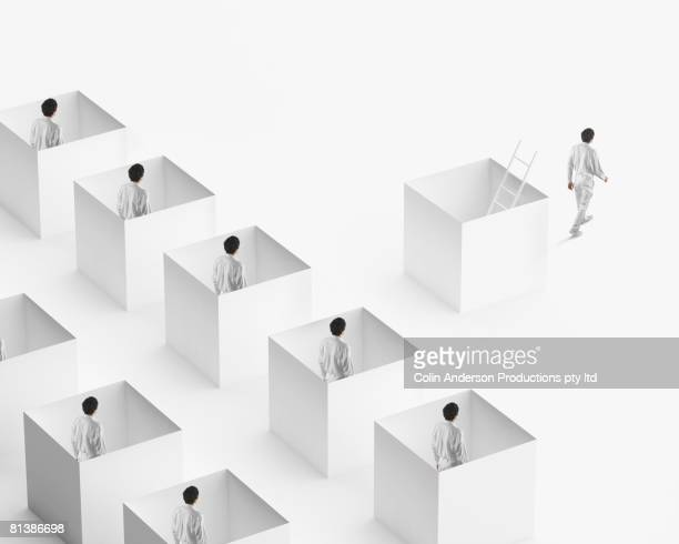 european businessman walking away from businessmen in boxes - repetition stock pictures, royalty-free photos & images