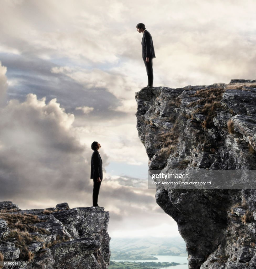 European businessmen on cliffs looking at each other : Stock Photo