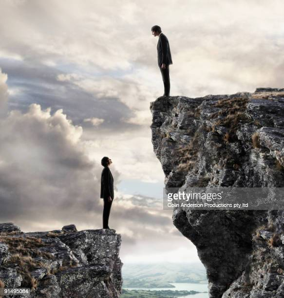 European businessmen on cliffs looking at each other
