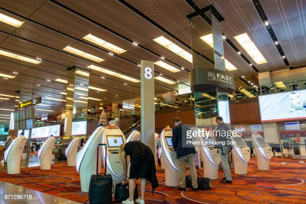 European businessmen using automated check-in system in Changi Airport, Singaport