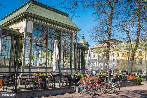 European cafe culture people enjoying sunshine outdoors restaurant Helsinki Finland
