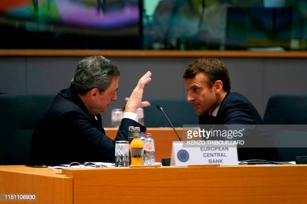 TOPSHOT European Central Bank President Mario Draghi and France's President Emmanuel Macron talk prior to a meeting during an EU summit at the Europa...