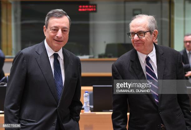 European Central Bank President Mario Draghi and Italian Finance Minister Pier Carlo Padoan look on during an Eurogroup meeting on December 4 2017 at...