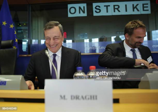 European Central Bank President Mario Draghi laughs before delivering speech during a meeting of the Committee on economic and monetary affairs in...