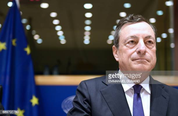 European Central Bank President Mario Draghi reacts as he delivers a speech during a meeting of the Committee on economic and monetary affairs at the...