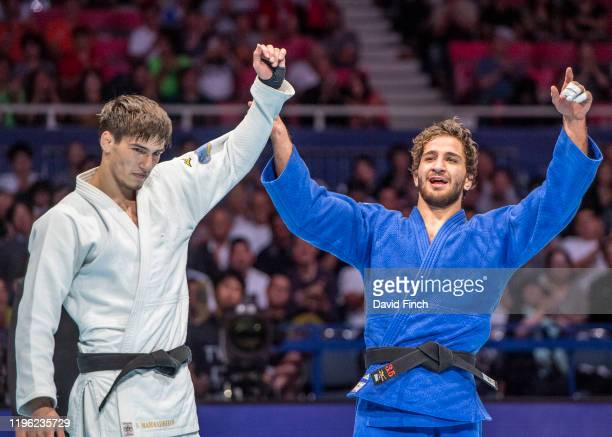 European champion Hidayat Heydarov of Azerbaijan holds up the hand of Somon Makhmadbekov of Tajikistan after throwing him in extratime for a wazari...