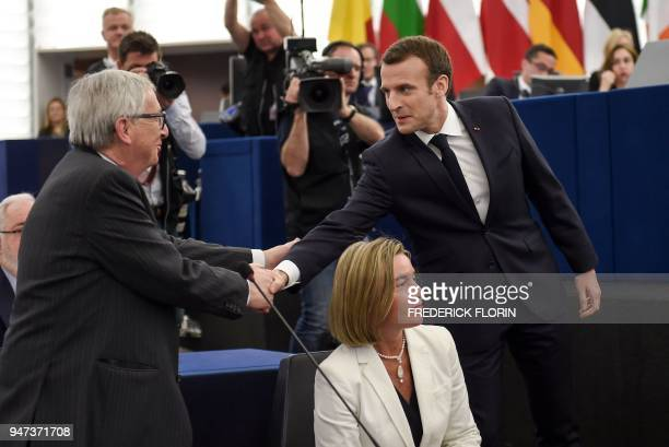 European Commission chief JeanClaude Juncker shakes hands with French President Emmanuel Macron as EU diplomatic chief Federica Mogherini looks on...
