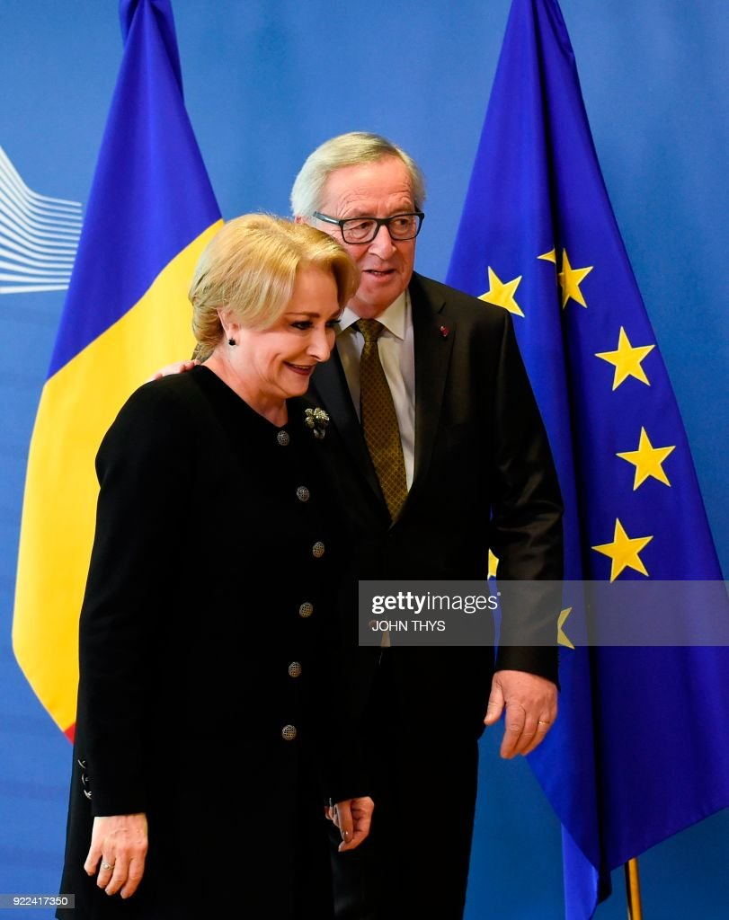 European Commission President Jean Claude Juncker (R) welcomes Romanian Prime Minister Viorica Dancila (L) before their bilateral meeting at the EU headquarters in Brussels on February 21, 2018. /