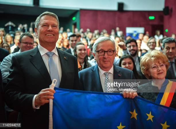 European Commission President JeanClaude Juncker and Romania's President Klaus Werner Iohannis pose with a European flag during the Young Citizen's...