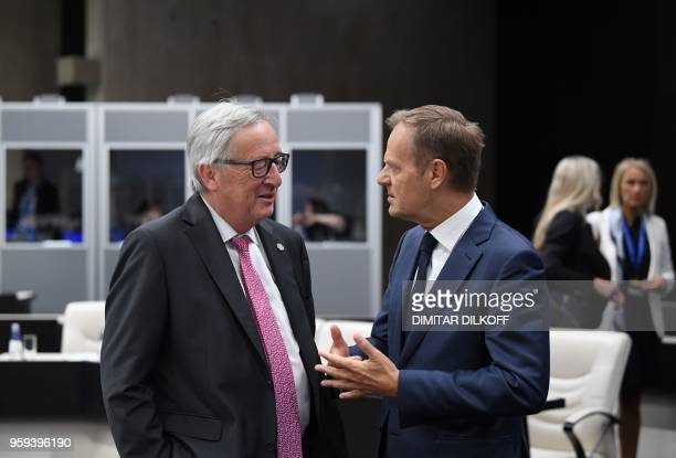 European Commission President JeanClaude Juncker speaks with European Council President Donald Tusk as they attend the EUWestern Balkans Summit in...