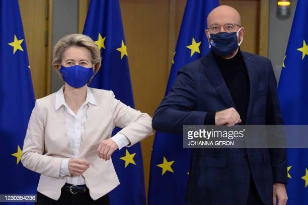European Commission President Ursula von der Leyen and European Council President Charles Michel bump their elbows in Brussels, on December 30 after...