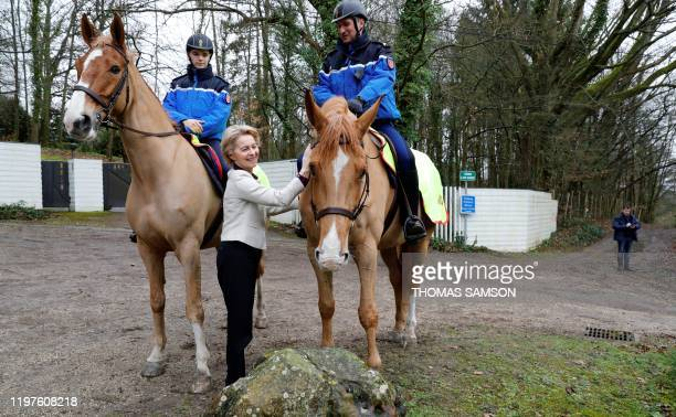 European Commission President Ursula von der Leyen caresses a horse of a French police officer in front of the house of French political economist...