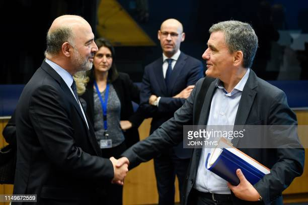 European Commissioner for Economic and Financial Affairs Taxation and Customs Pierre Moscovici shakes hands as he talks with Greek Finance Minister...