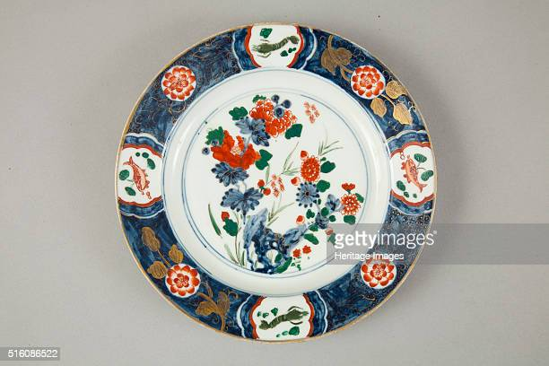 A European copy of a Chinese Imari plate decorated in the centre with floral group of peonies issuing from rock and bamboo The cavetto is undecorated...