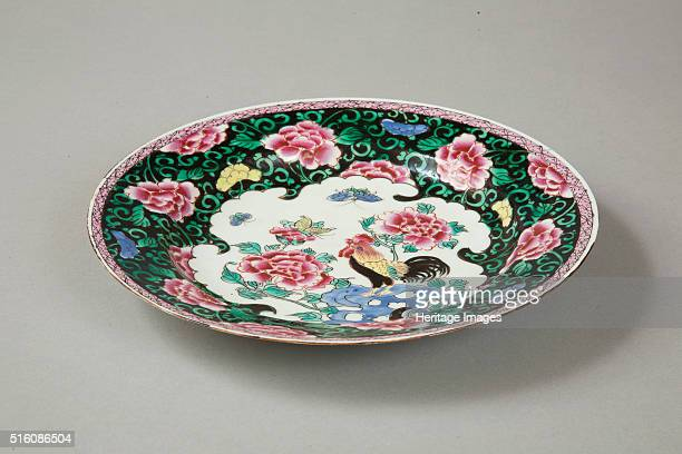 A European copy of a famille noire plate with pink peonies amid floral sprays on a black glazed ground round cavetto and rim In the centre is a petal...