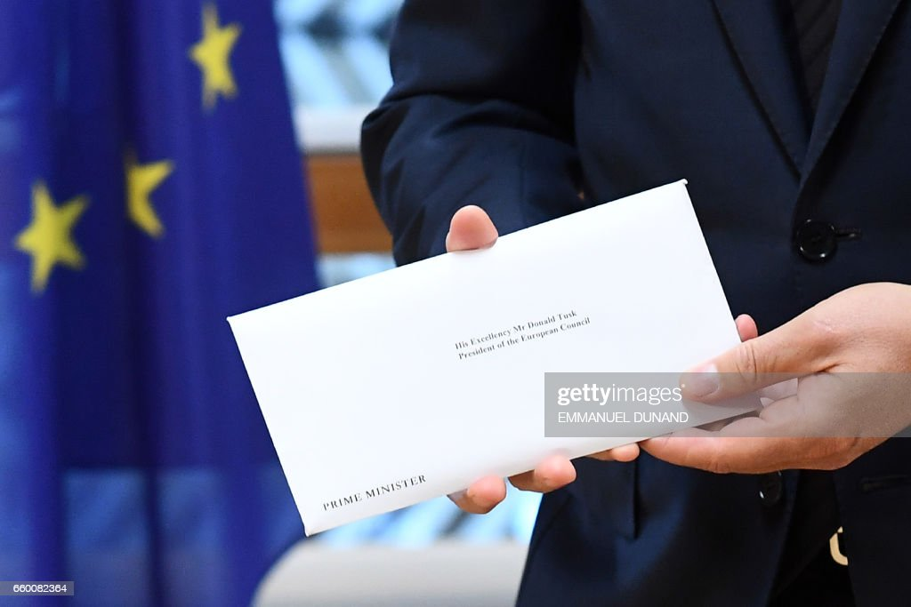 TOPSHOT - European Council President Donald Tusk holds British Prime Minister Theresa May's formal notice of the UK's intention to leave the bloc under Article 50 of the EU's Lisbon Treaty in Brussels on March 29, 2017. Britain formally launches the process for leaving the European Union on Wednesday, a historic step that has divided the country and thrown into question the future of the European unity project. / AFP PHOTO / POOL / Emmanuel DUNAND