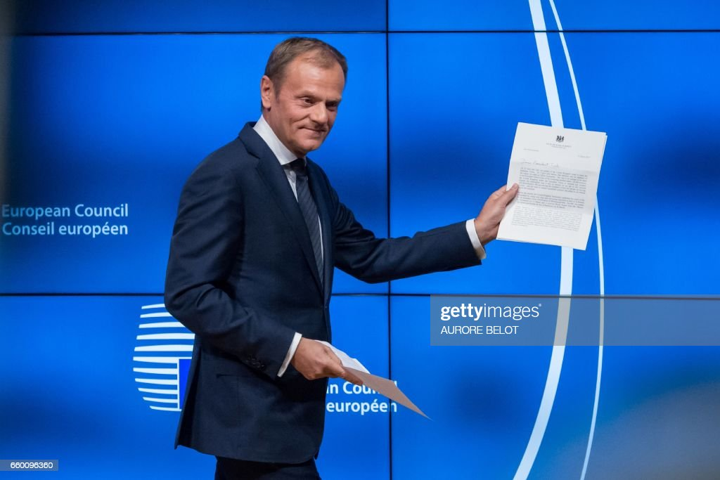 TOPSHOT - European Council President Donald Tusk holds the formal notice launching the Brexit as he arrives to give a press conference, in Brussels on March 29, 2017. Britain formally launches the process for leaving the European Union on Wednesday, a historic step that has divided the country and thrown into question the future of the European unity project. / AFP PHOTO / Aurore Belot