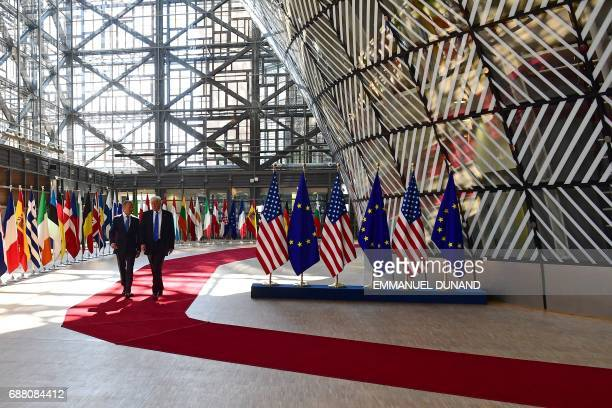 European Council President Donald Tusk speaks to US President Donald Trump after welcoming him at EU headquarters as part of the NATO meeting in...