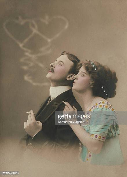 A European couple of the Victorian era smoke cigarettes together and blow smoke rings in the air that form interlocking hearts