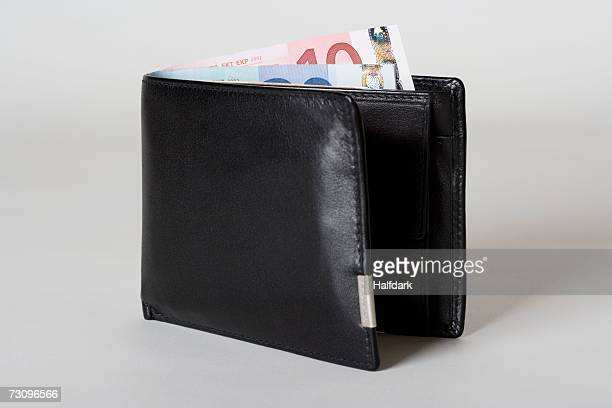 European currency poking out of black leather wallet