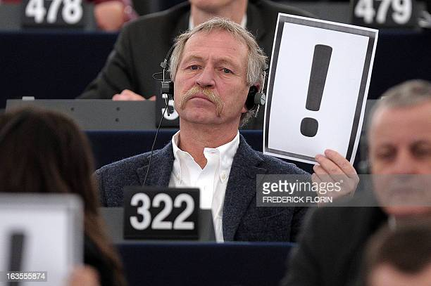 European Deputy Jose Bove holds on march 12 2013 a placard bearing an exclamation mark during a session at the European Parliament in Strasbourg...