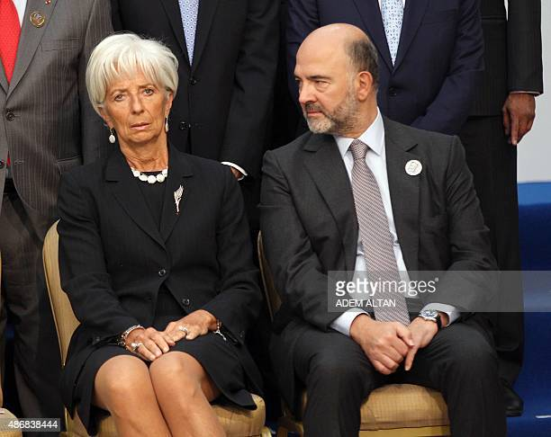 European Economic and Financial Affairs Commissioner Pierre Moscovici looks at International Monetary Fund Managing Director Christine Lagarde as...