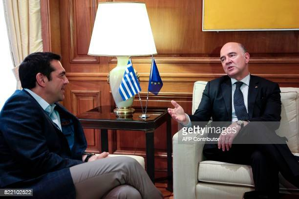 European Economic and Financial Affairs Commissioner Pierre Moscovici speaks with Greek Prime Minister Alexis Tsipras during a meeting at the Maximou...