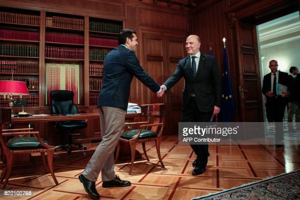European Economic and Financial Affairs Commissioner Pierre Moscovici shakes hands with Greek Prime Minister Alexis Tsipras during a meeting at the...