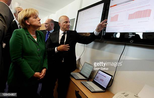 European Energy Exchange Chairman Hans-Bernd Menzel explains the development of the days's electricity prices on a graph to German Chancellor Angela...