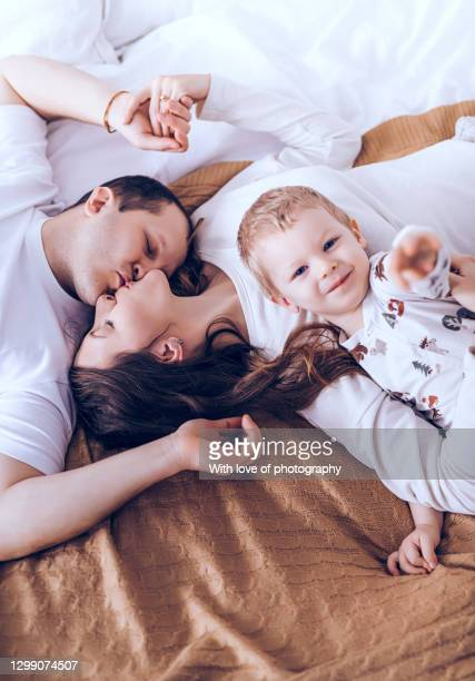 european family with one child, 2 years little boy with parents at home in pajamas - 30 39 years stock-fotos und bilder