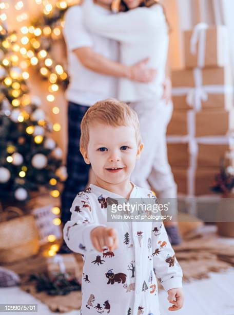 european family with one child, 2 years little boy with parents at home in pajamas on christmas and new year holidays - 30 39 years stock-fotos und bilder