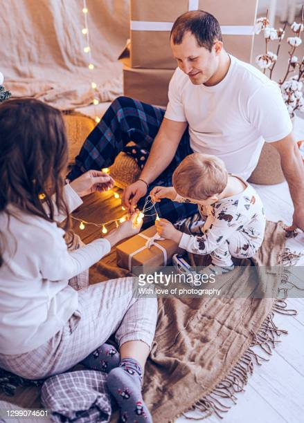european family with one child with christmas tree, 2 years little boy with parents at home in pajamas on christmas and new year holidays - 30 39 years stock-fotos und bilder